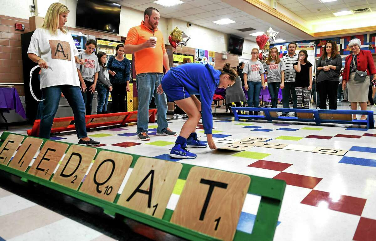West Haven's Bailey Middle School teachers Cindi Anastasio, left, and Sean Griffin, center, serve as referees and scorekeepers as they watch seventh-grader Jacquelyn Tavelia play Scrabble, right, on a life-size playing board.