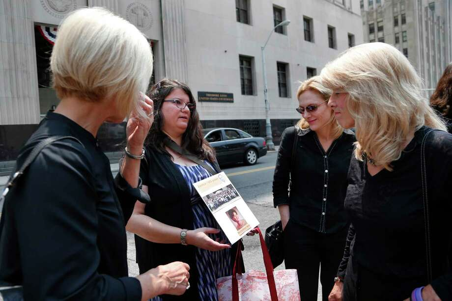 """Liz Lupo, second from left, shows a sign in honor of her mother, Marianne Lupo, a former patient of Dr. Farid Fata, outside federal court, Monday, July 6, 2015, in Detroit. Patients of Fata received """"stunning"""" doses of a powerful, expensive drug that exposed them to life-threatening infections, an expert testified Monday as a judge heard details about a cancer specialist who fleeced insurance companies and harmed hundreds of people. (AP Photo/Paul Sancya) Photo: AP / AP"""