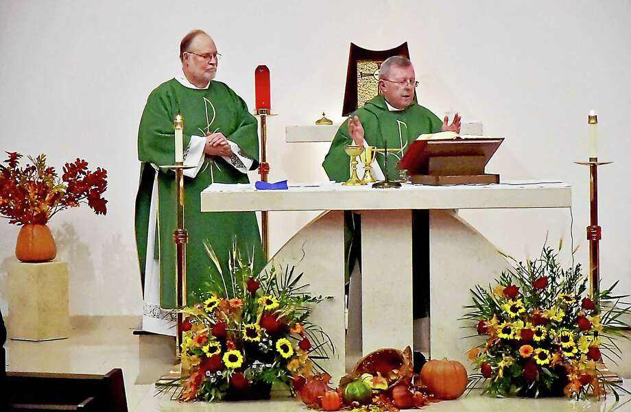 Deacon Stephen Yatcko, at left, assists Rev. Daniel J. Sullivan, pastor of Our Lady of Mount Carmel Church celebrate Saturday vigil at St. Joan of Arc Church. Photo: Catherine Avalone — New Haven Register / New Haven RegisterThe Middletown Press