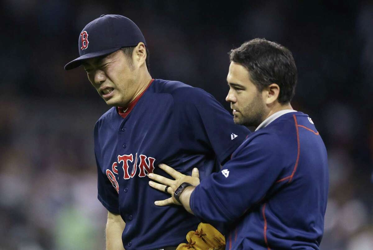 Boston Red Sox closer Koji Uehara is helped off the field after a game against the Tigers on Friday in Detroit.