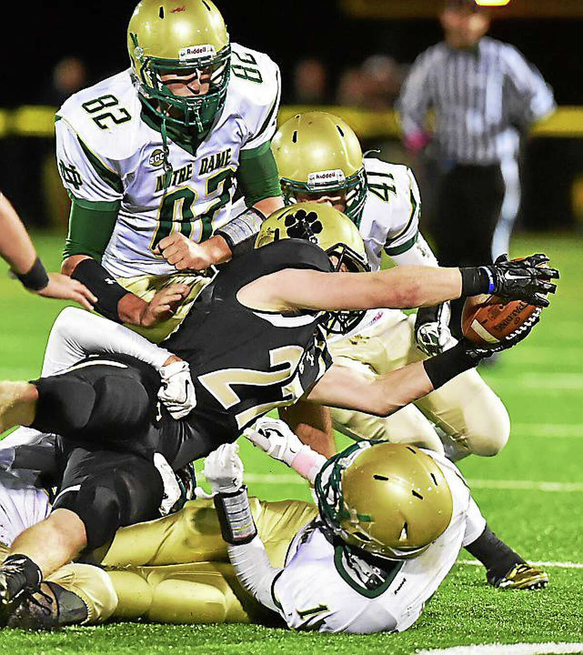 Norte Dame-West Haven's Kameron Matthews, Frank Longley and Prince Brooks tackle Hand's Ryan Kaufmann earlier this year.