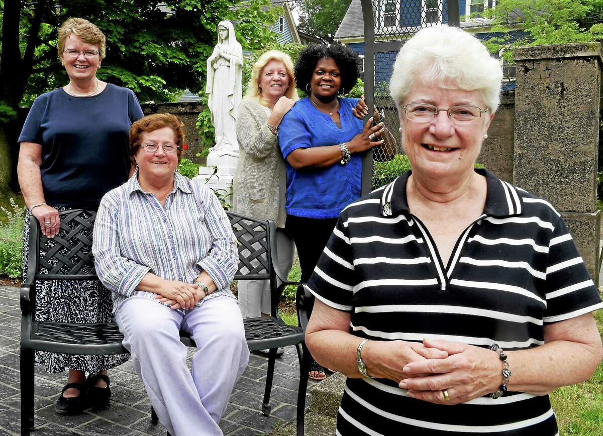 Sharing memories of the former St. Mary's High School in New Haven, from left to right, Sister Rosemary Reynolds, SND, class of 1969 and a guidance counselor at the school from 1985-1989; Teresa Sirico of Milford, class of 1966; Deborah Frattini of East Haven, a teacher there from 1978-1991; Morganna Payne of New Haven, class of 1987; and Sister Anne Kilbride, OP, Class of 1960 and principal and teacher there from 1977-1988, as they plan for an all-class reunion, pose by St. Mary statue at Albertus Magnus College Wednesday July 15, 2015.