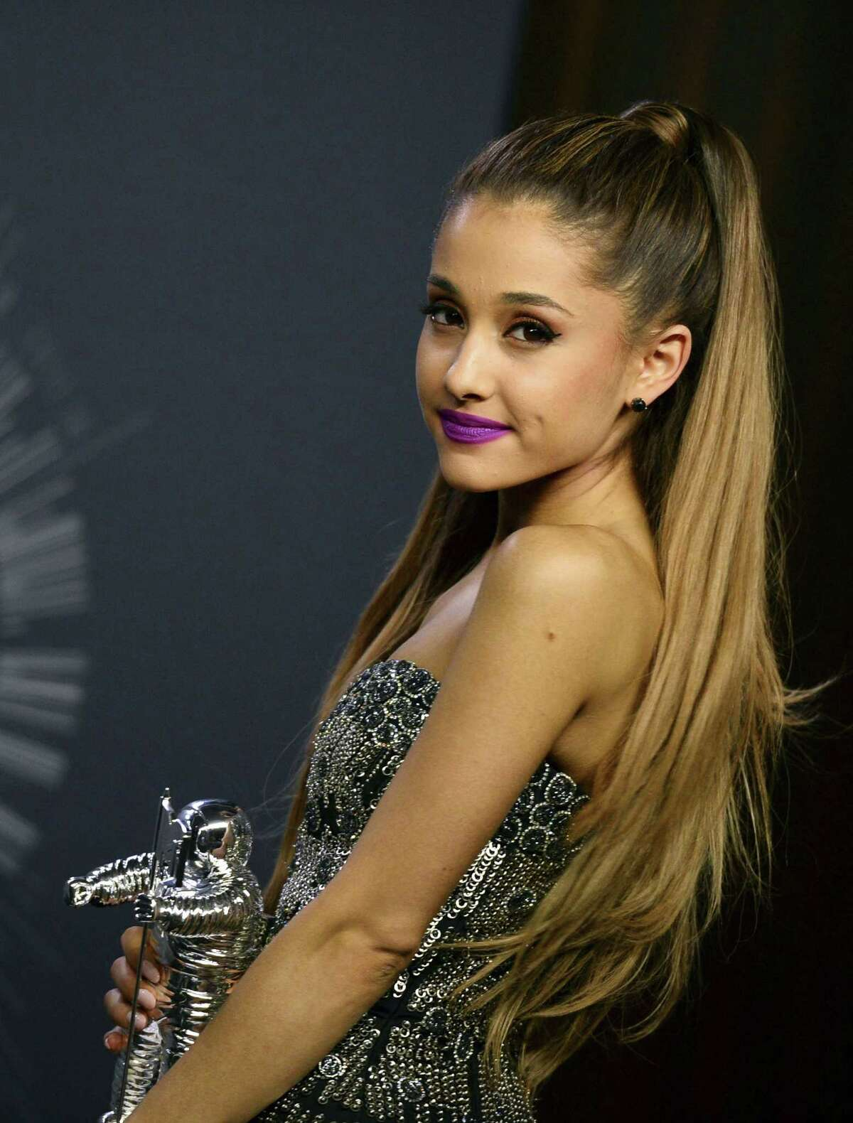 FILE - In this Aug. 24, 2014 file photo, Ariana Grande poses with her award for Best Pop Video in the press room at the MTV Video Music Awards in Inglewood, Calif. Grande has apologized for licking doughnuts and speaking harsh words about America for a second time in a new video. The singer said in the clip posted late Thursday, July 9, 2015, that sheís ìdisgusted with myself.î She added that she didnít clearly convey her true feelings in her first apology _ a written statement where she ranted about obesity in America. (Photo by Jordan Strauss/Invision/AP, File)