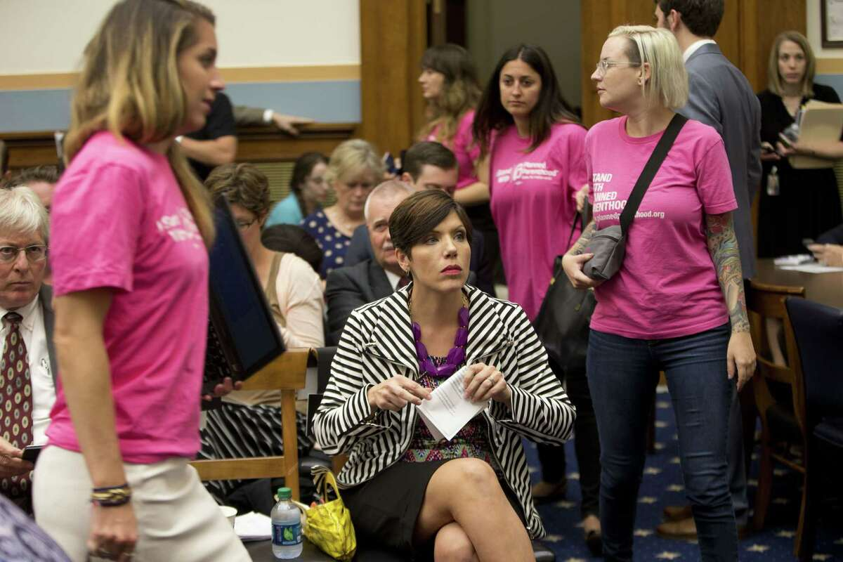 As supporters of Planned Parenthood look for seats, Melissa Ohden, center, pro-life supporter from Gladstone, MO., waits to testify before the House Judiciary Committee hearing at the Capitol in Washington. The committee was examining the abortion practices of Planned Parenthood, Wednesday, Sept. 9, 2015. Today's hearing is Congress' first since the Center for Medical Progress, a small group of anti-abortion activists, began releasing videos in July showing Planned Parenthood officials casually describing how they sometimes obtain tissue from aborted fetuses for medical researchers. Backed by analysts it hired, Planned Parenthood has said the videos were dishonestly edited to distort its officials' remarks and has denied any wrongdoing.