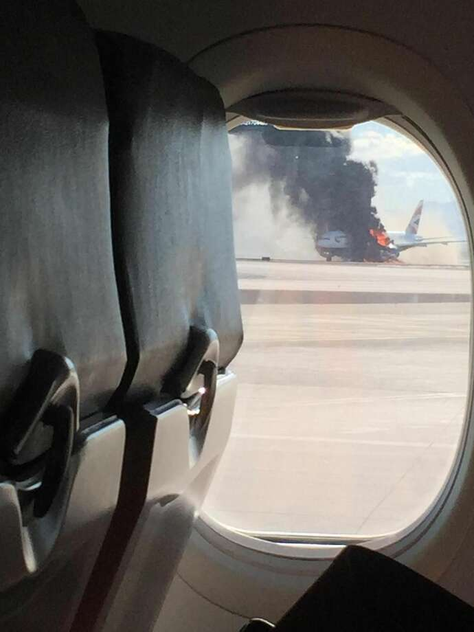 In this photo provided by David Somers and taken from the view of a plane window, smoke billows out from a plane that caught fire at McCarren International Airport, Tuesday, Sept. 8, 2015, in Las Vegas. An engine on the British Airways plane caught fire before takeoff, forcing passengers to escape on emergency slides. Photo: David Somers Via AP    / David Somers