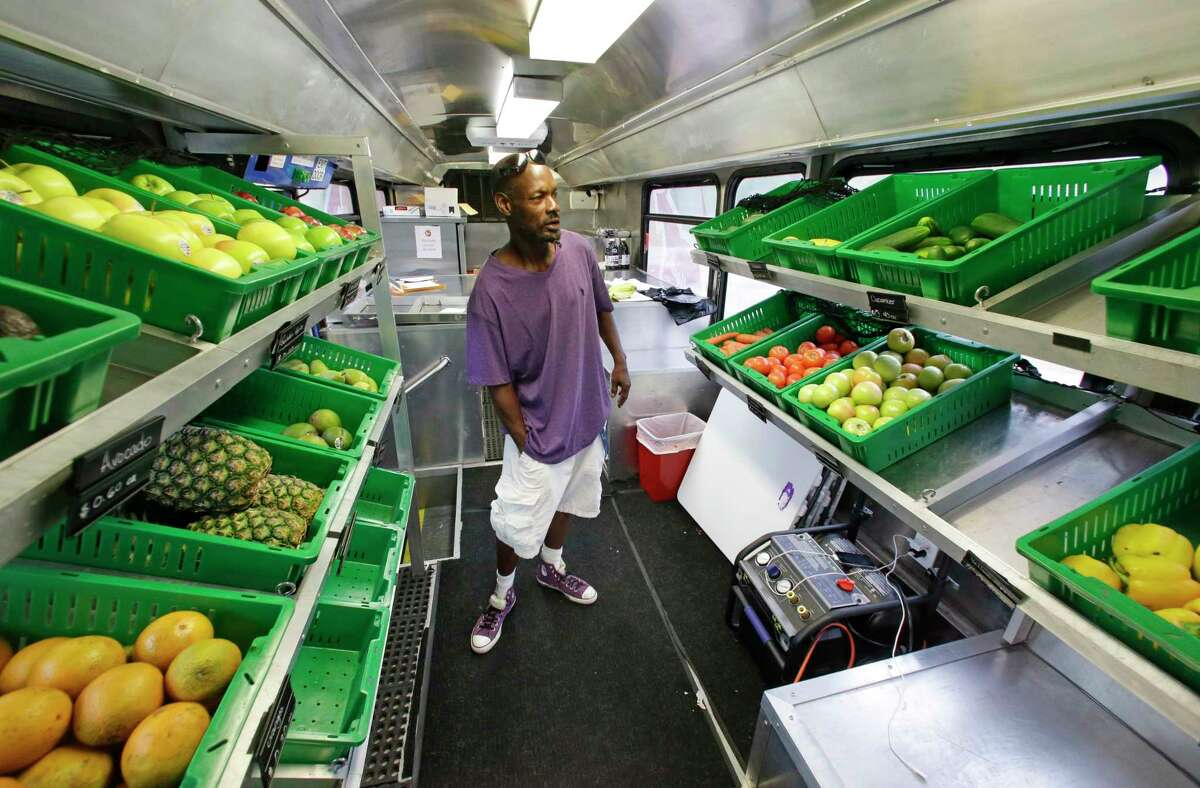 In this July 15, 2015 photo, Jock Riggins looks over the fresh fruits and vegetables on the Fresh Stop bus, a mobile market, in Eatonville, Fla. The Fresh Stop brings fresh fruits and vegetables to communities with no supermarkets. The nation's largest grocery chains have built new supermarkets in only a fraction of the neighborhoods where they're needed most, according to an analysis of federal food stamp data by The Associated Press.