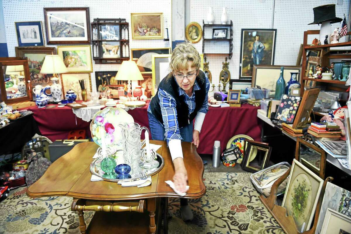 Marilyn Hegarty of Clinton dusts off a table in her booth at the Grass Island Flea Market in Guilford on 10/4/2015. The market will close on Oct. 25.