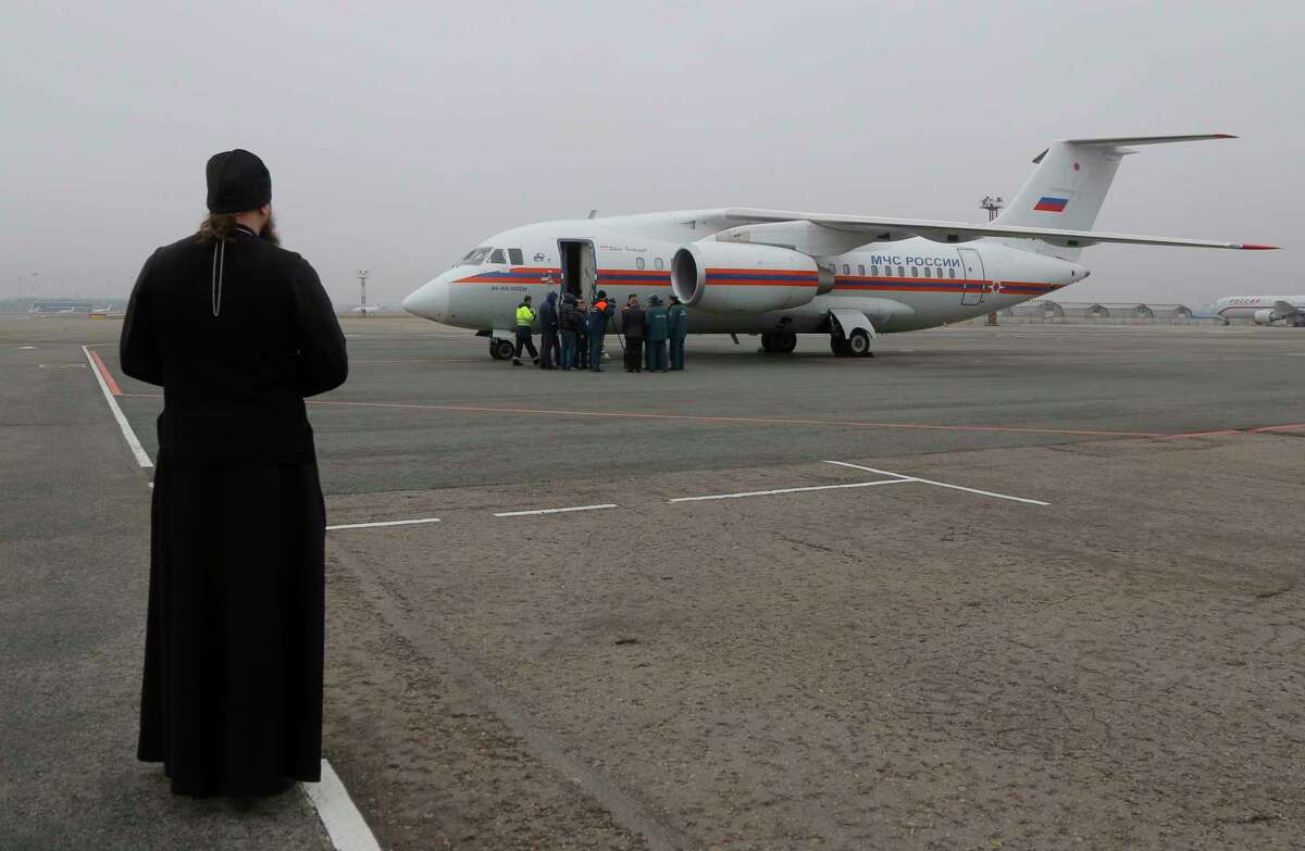 An Orthodox priest looks on as a Russian Ministry for Emergency Situations plane carries the bodies of victims from the plane crash at Pulkovo airport outside St. Petersburg, Russia, Friday, Nov. 6, 2015. All 224 people onboard a Russian jet en route from the Red Sea resort of Sharm el-Sheikh to Russia's St. Petersburg were killed in Saturday's plane crash.