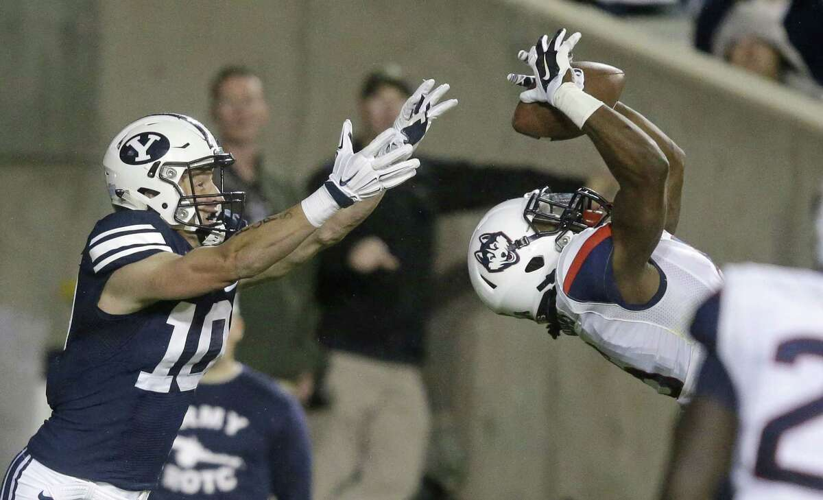 UConn cornerback Jhavon Williams, right, picks of a pass intended for BYU wide receiver Mitch Mathews, left, in the first half of an Oct. 2 game.