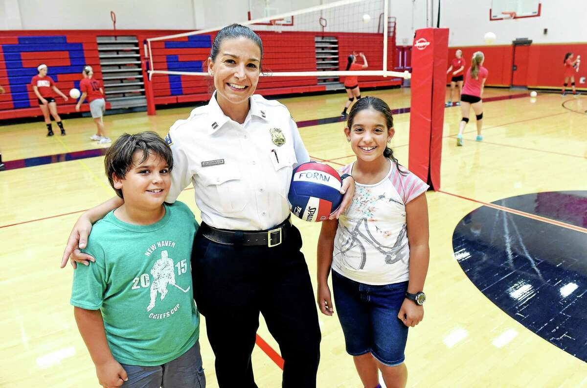 New Haven Police Captain and Foran Girls Volleyball Coach Julie Johnson is photographed with her two children, Daniel, 8, and Jenna, 10, in the gymnasium at Foran High School in Milford on Sept. 3.