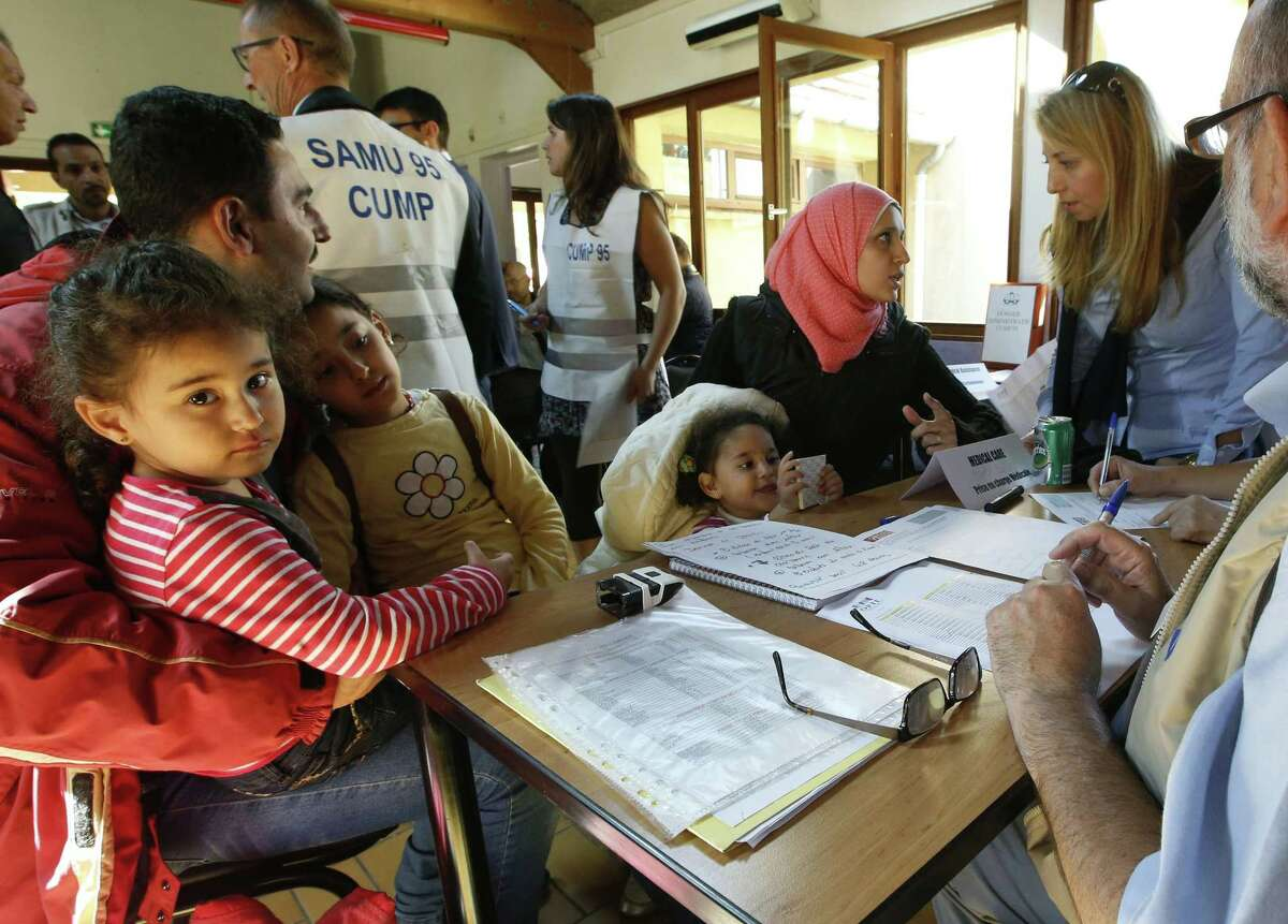 Refugees from Syria and Irak speak with doctors for a medical check after they arrive at the Hubert Renaud centre in Cergy-Pontoise near Paris on Wednesday. The groups is the first among around 1,000 that French President Francois Hollande pledged to receive from the neighboring country Germany.