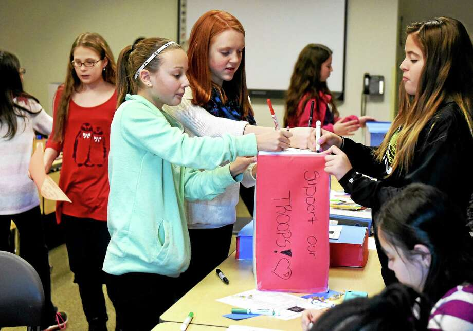 Members of Hamden Middle School's Student Ambassadors Club prepare boxes Monday that will be mailed to a Hamden native and his unit serving in Iraq. Photo: Peter Hvizdak — New Haven Register   / ©2015 Peter Hvizdak