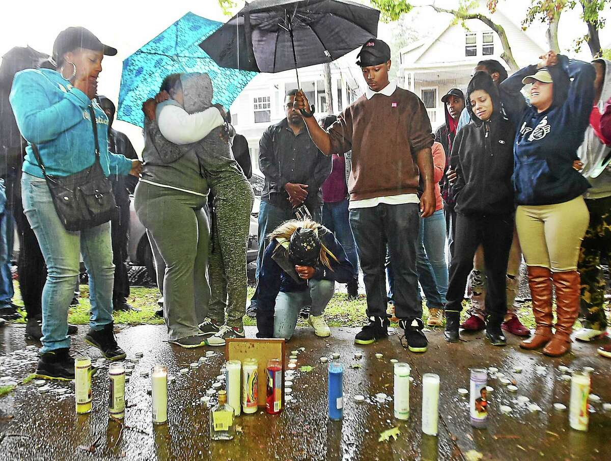Jackie Heath hugs a friend holding a blue umbrella during a vigil for her 29-year-old son Antoine Heath during a downpour on Chapel Street in New Haven in close proximity to where Heath was found shot.