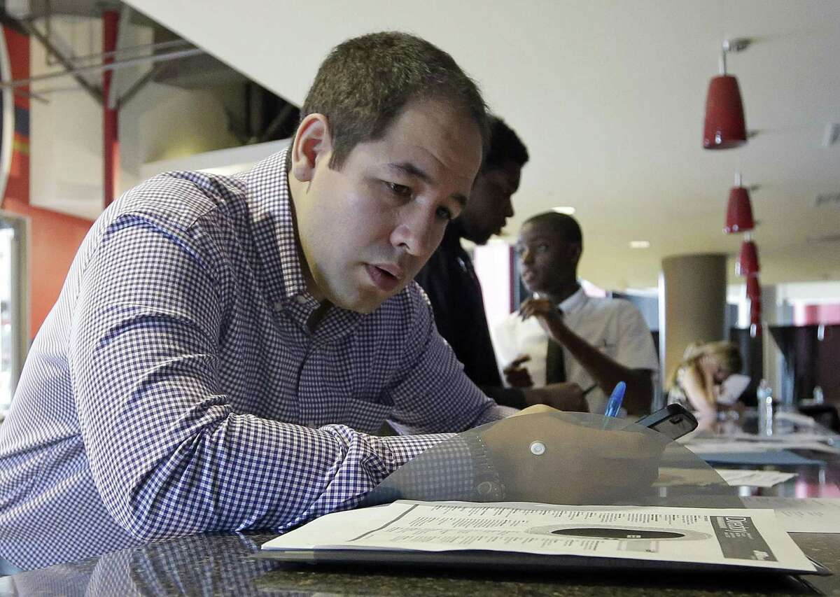 In this file photo taken Wednesday, June 10, 2015, Luis Duran fills out a job application during a job fair in Sunrise, Fla.
