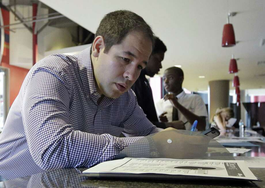 In this file photo taken Wednesday, June 10, 2015, Luis Duran fills out a job application during a job fair in Sunrise, Fla. Photo: (AP Photo/Alan Diaz) / AP