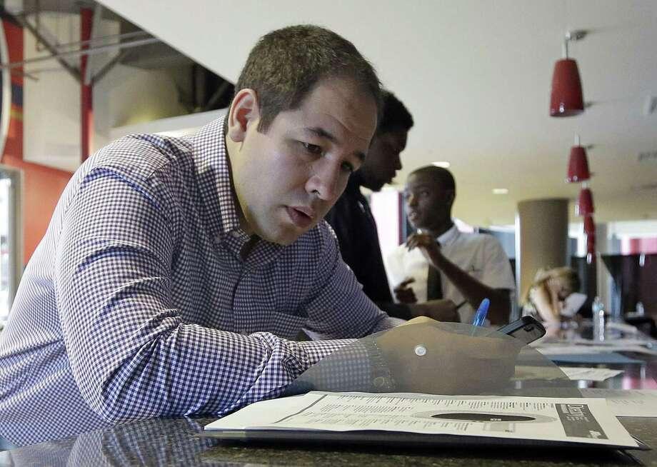 In this file photo taken Wednesday, June 10, 2015, Luis Duran fills out a job application during a job fair in Sunrise, Fla. Photo: (AP Photo/Alan Diaz) / AP