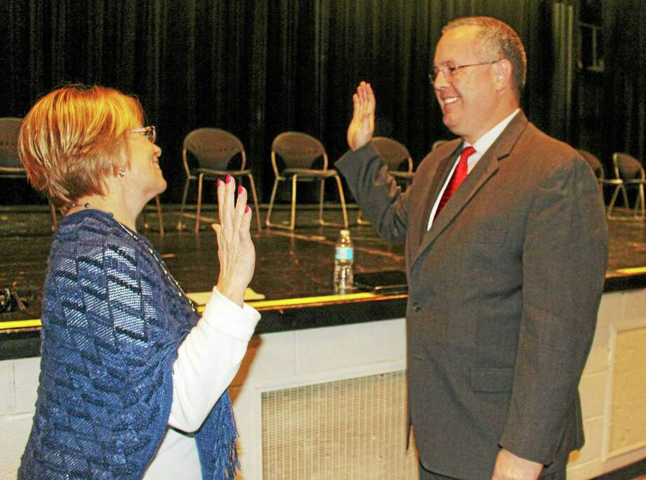 First Selectman Kurt Miller, right, takes the oath of office Monday from Town Clerk Susan DeBarber. Photo: Jean Falbo-Sosnovich — New Haven Register
