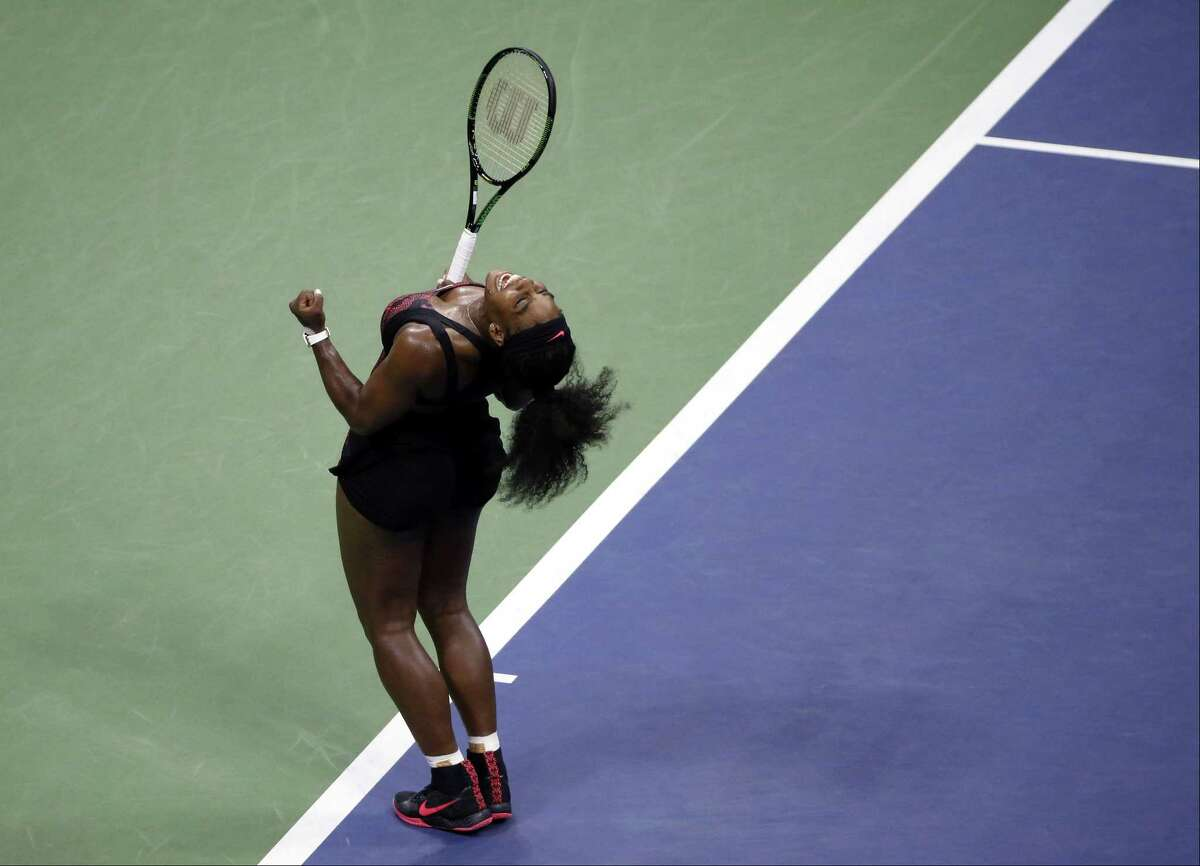 Serena Williams reacts after beating Venus Williams during a quarterfinal match at the U.S. Open.