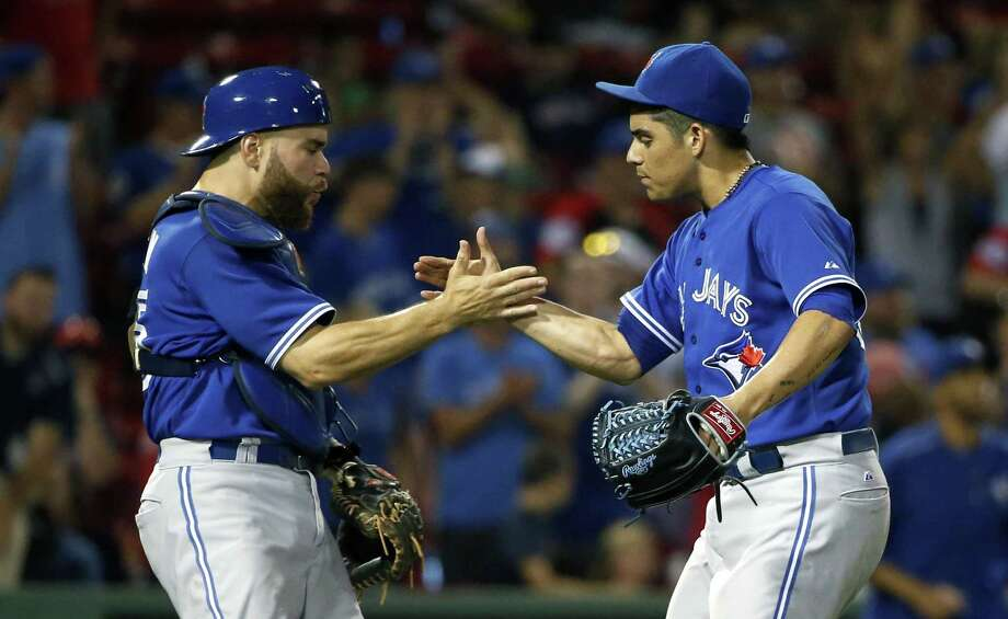Toronto Blue Jays' Roberto Osuna, right, and Russell Martin celebrate after the Blue Jays defeated the Boston Red Sox 5-1 in 10 innings during a baseball game in Boston, Tuesday, Sept. 8, 2015. (AP Photo/Michael Dwyer) Photo: AP / AP