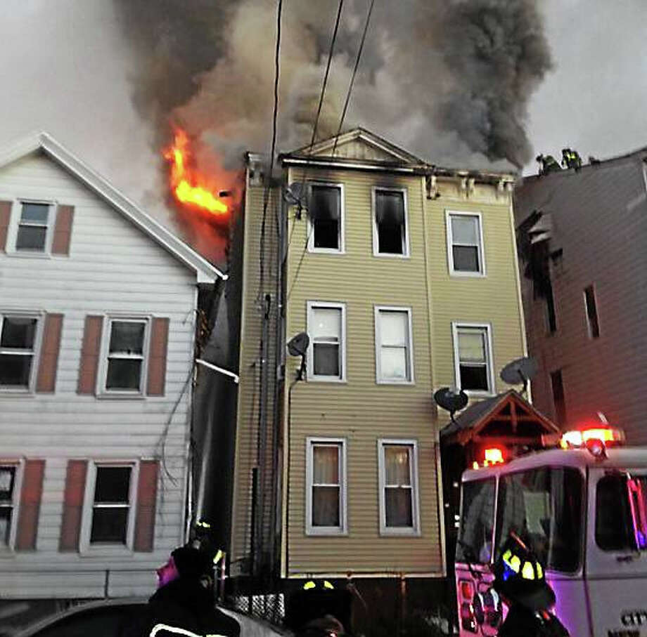 New Haven firefighters work to put out a blaze at a home at 153 Clay St. in New Haven. (Photo via @NewHavenFire on Twitter) Photo: Journal Register Co.