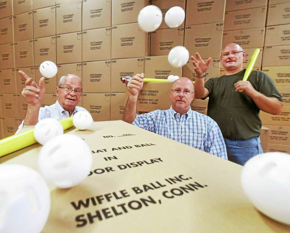 Founder of the Wiffle Ball David A. Mullany, left, and his sons David J. Mullany, center, and Stephen Mullany, owners of Wiffle Ball Inc. of Shelton, are seen in a company warehouse.