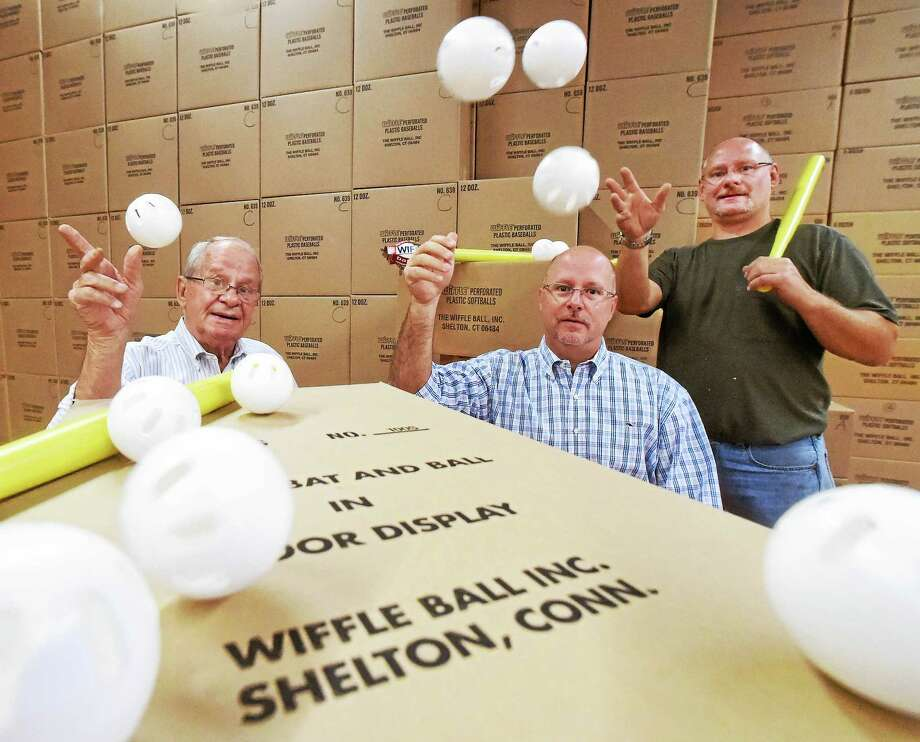 Founder of the Wiffle Ball David A. Mullany, left, and his sons David J. Mullany, center, and Stephen Mullany, owners of Wiffle Ball Inc. of Shelton, are seen in a company warehouse. Photo: Peter Hvizdak — New Haven Register   / ©2015 Peter Hvizdak