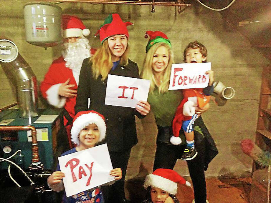 "Pam McLoughlin's family is hoping others will ""Pay it Forward""  after they received a gift of a furnace and installation from two area companies. Back row left to right: the family's new boiler, Will - who likes to dress as Santa this time of year. Front from left to right: Caleb, 6, Kathleen, Debbie, Elijah, 3, Isaiah, 8. Photo: Journal Register Co."