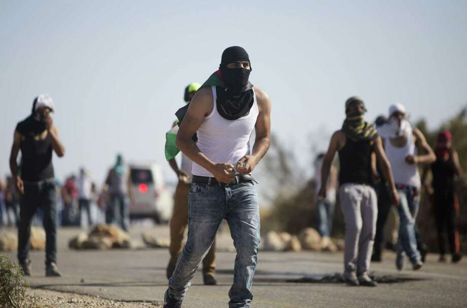 Palestinian demonstrators throw stones toward Israeli security forces during clashes after the funeral of Palestinian Saed Dawabsheh, 32, in the West Bank village of Duma near Nablus on Aug. 8, 2015. The father of a Palestinian toddler killed in a July 31 firebomb attack blamed on Jewish extremists has died of wounds sustained in the same incident, his family said Saturday. His 18-month-old toddler perished in the flames, while his 4-year-old brother and parents were seriously hurt. Photo: AP Photo/Majdi Mohammed   / AP