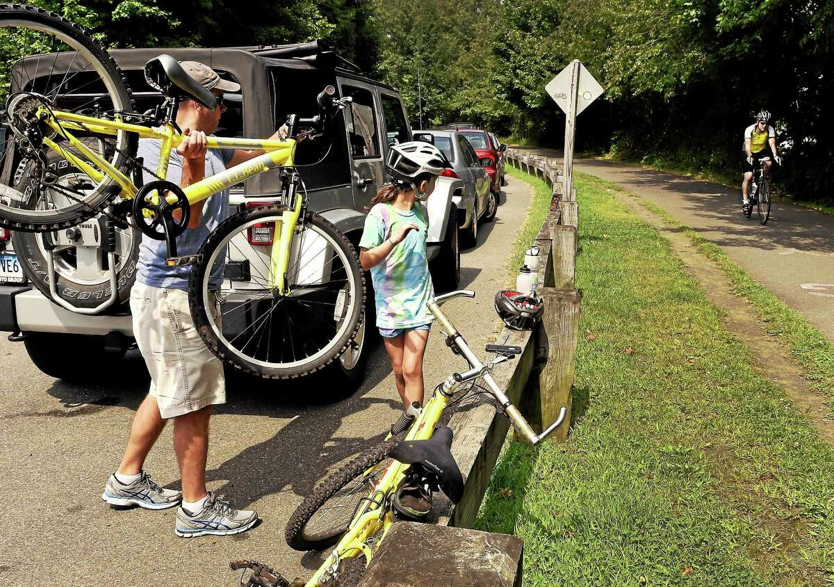 PETER HVIZDAK — NEW HAVEN REGISTER Jamison Scott of Woodbridge and his daughter Caroline, 8, prepare for a bike ride along the Farmington Canal Trail by Todd Street near Whitney Avenue in Hamden recently.