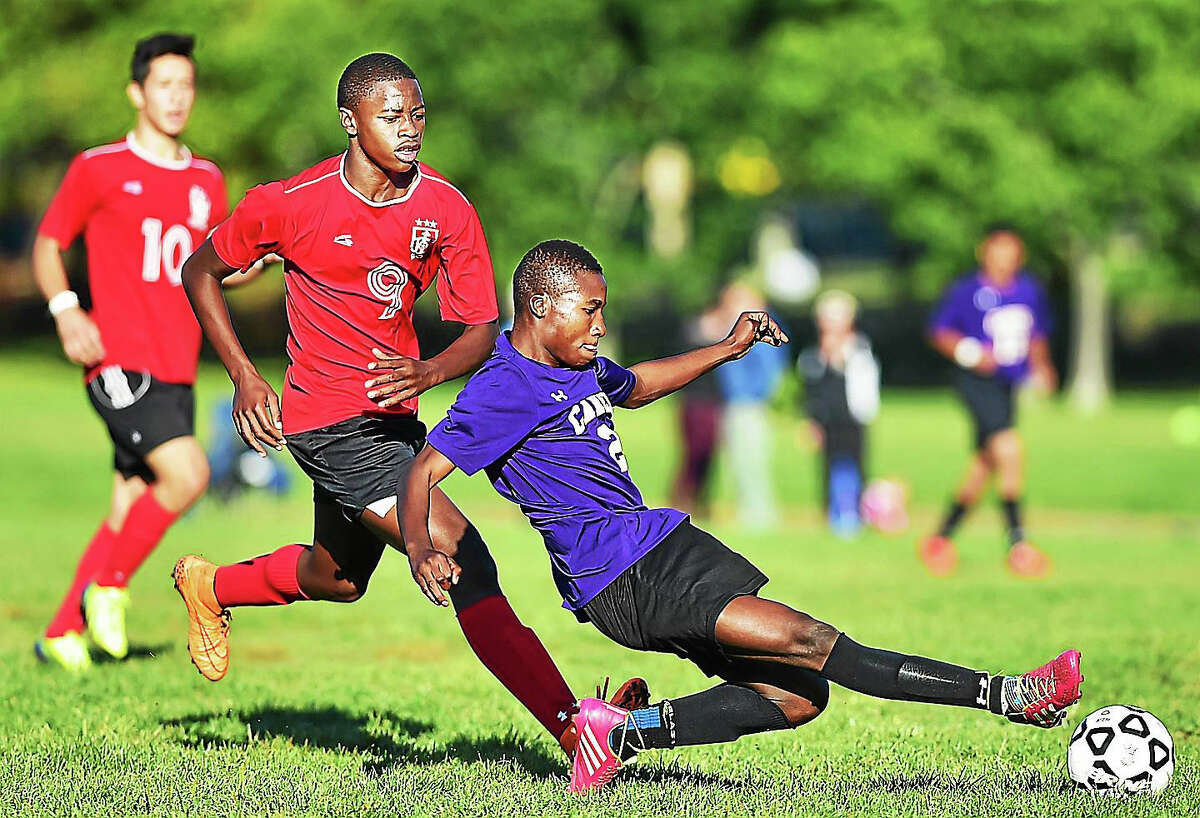 Career's Mrdochee Bouanga on attack as Wilbur Cross' Mohamed Kane defends which ended in a 1-1 tie Wednesday at East Shore Field in New Haven.