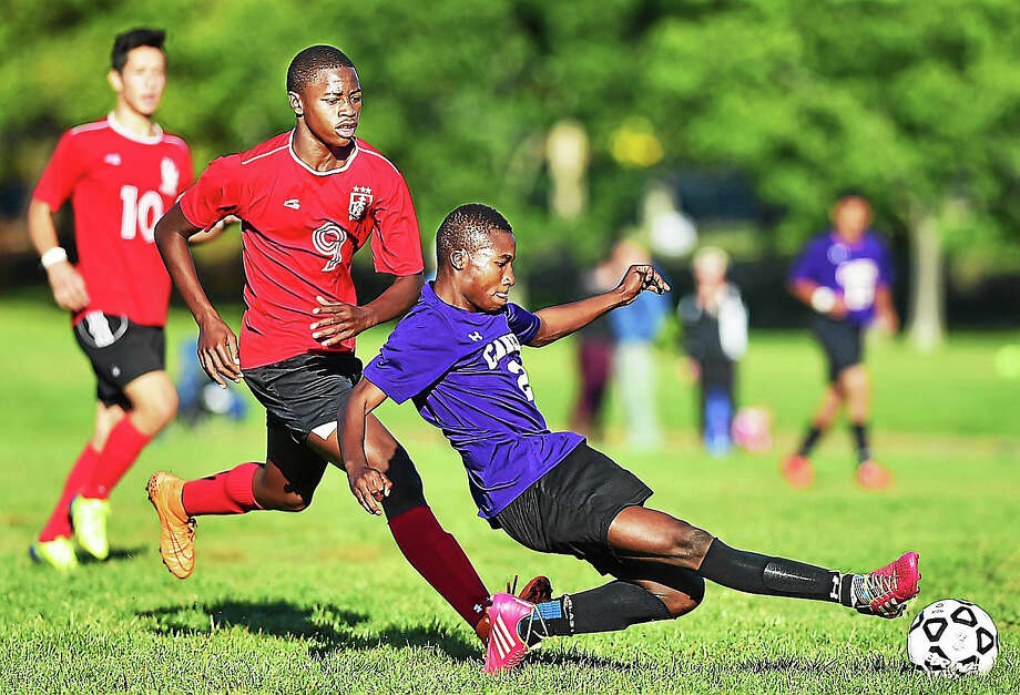 Career's Mrdochee Bouanga on attack as Wilbur Cross' Mohamed Kane defends which ended in a 1-1 tie Wednesday at East Shore Field in New Haven. Photo: Catherine Avalone/New Haven Register   / Catherine Avalone/New Haven Register