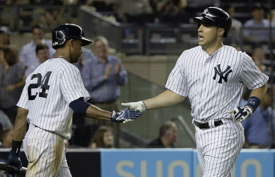 The Yankees' Mark Teixeira, right, is greeted by Chris Young after hitting a solo home run against the Oakland Athletics. Photo: Julie Jacobson  — The Associated Press   / AP