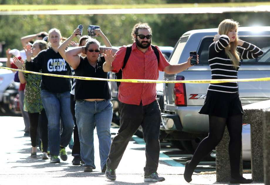 In this Thursday, Oct. 1, 2015 photo, students, staff and faculty are evacuated from Umpqua Community College in Roseburg, Ore., after a deadly shooting. Chris Harper-Mercer took multiple lives Thursday before killing himself as officers closed. Photo: Michael Sullivan /The News-Review Via AP, File   / The News-Review