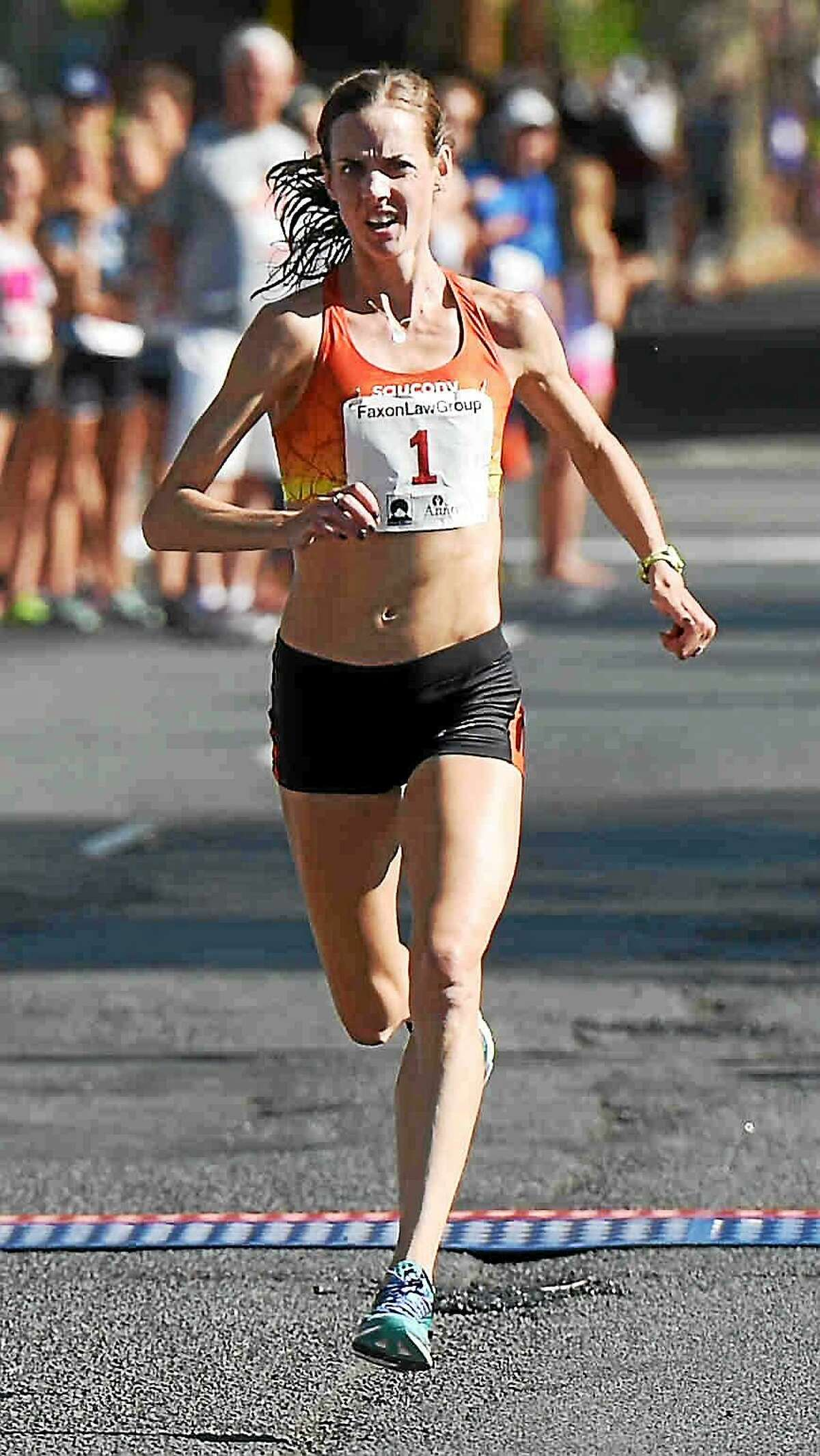 Molly Huddle runs towards the Temple Street finish line, winning the 2015 Faxon Law New Haven Road Race Women's 20K and the 20K Women's National Championship in New Haven, Connecticut, Monday, Sept. 7, 2015, with a time of 1:06.26.