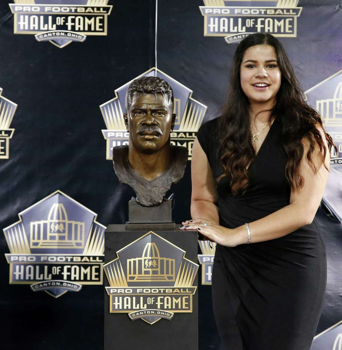 Sydney Seau, daughter of former NFL player Junior Seau, poses with a bust of her father Saturday.