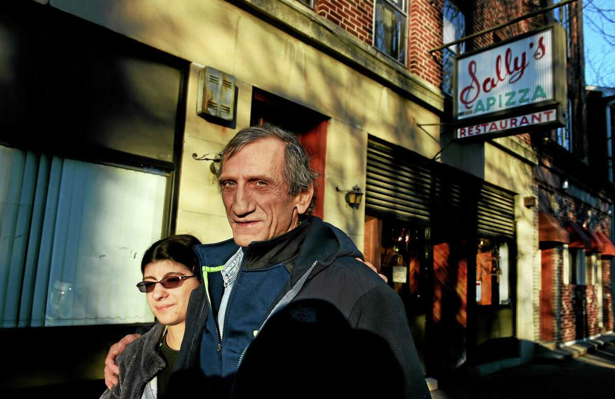 Rich Consiglio, one of the owners of Sally's Apizza, right, with his daughter, Hannah, in front of the iconic Wooster Street pizzeria in New Haven Friday.
