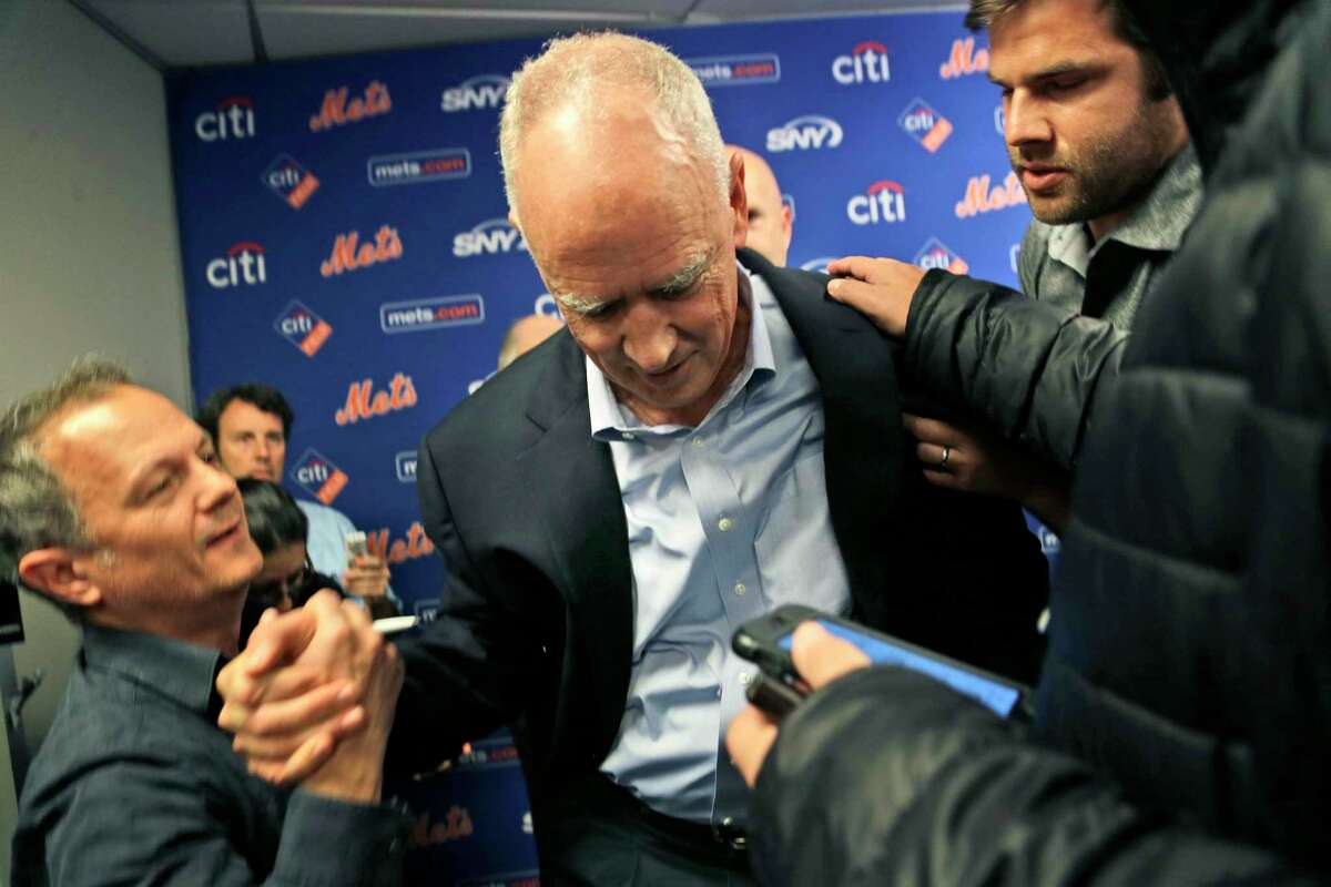 New York Mets general manager Sandy Alderson is assisted to his feet by reporters after collapsing during a news conference on Wednesday in New York.