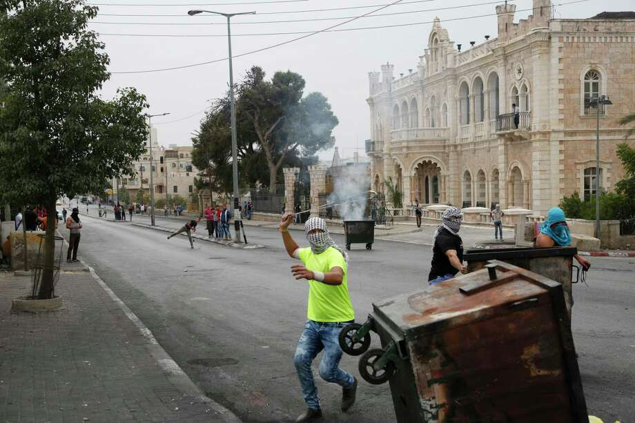 This Friday, Oct. 23, 2015, photograph shows Palestinians clashing with Israeli troops in front of the Intercontinental hotel in the West Bank city of Bethlehem. The century-old Jacir Palace hotel, with its soaring stone archways and wrought iron balconies, was once a symbol of Bethlehem's wealth and tourism potential. Today, the property reflects the city's dour mood ahead of the crucial Christmas season after months of unrest that has taken more than 100 lives, including a Palestinian waiter from the hotel. Photo: AP Photo/Nasser Shiyoukhi    / AP