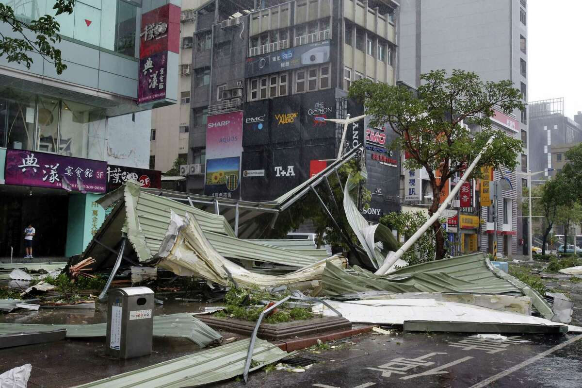 A street corner is filled with a mangled rooftop brought down by strong winds from Typhoon Soudelor in Taipei, Taiwan, Saturday, Aug. 8, 2015. Soudelor brought heavy rains and strong winds to the island Saturday with winds speeds over 170 km per hour (100 mph) and gusts over 200 km per hour (120 mph) according to Taiwan's Central Weather Bureau.