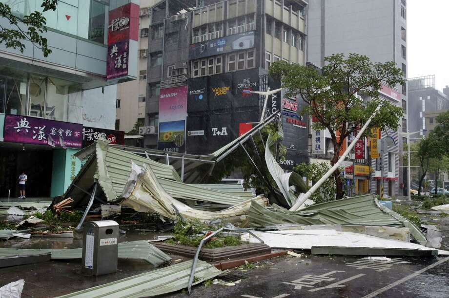 A street corner is filled with a mangled rooftop brought down by strong winds from Typhoon Soudelor in Taipei, Taiwan, Saturday, Aug. 8, 2015. Soudelor brought heavy rains and strong winds to the island Saturday with winds speeds over 170 km per hour (100 mph) and gusts over 200 km per hour (120 mph) according to Taiwan's Central Weather Bureau. Photo: AP Photo/Wally Santana / AP