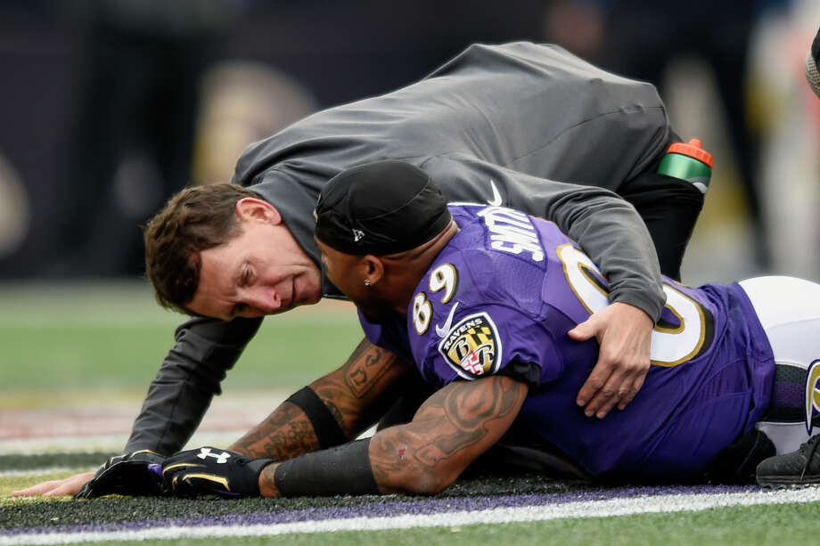 A trainer tends to Ravens receiver Steve Smith after an injury Sunday against the San Diego Chargers in Baltimore. Photo: Gail Burton — The Associated Press   / FR4095 AP