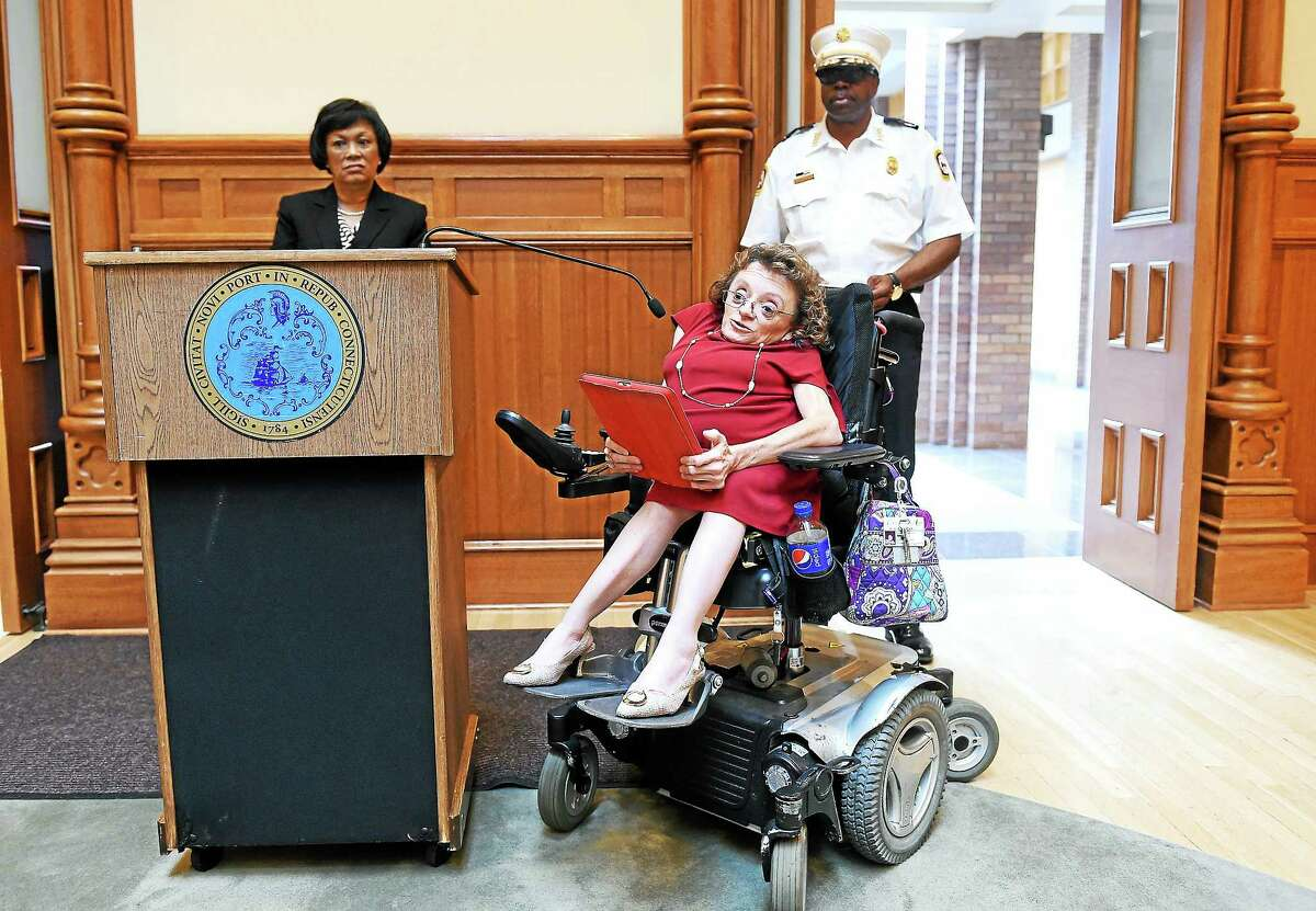 Michelle Duprey (center), director of the Depatment of Services for Persons with Disabilities of New Haven, speaks at a press conference on the anniversary of the Americans with Disabilities Act at City Hall in New Haven in 2014.
