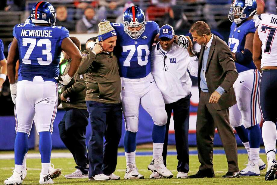 New York Giants center Weston Richburg (70) is helped off the field during a Nov. 15 game against the Patriots. Photo: Julio Cortez — The Associated Press File Photo   / AP