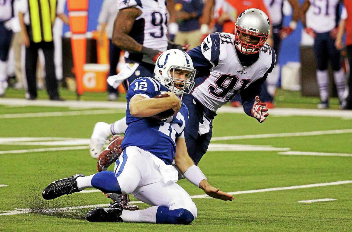 Indianapolis Colts quarterback Andrew Luck slides with the ball as New England Patriots linebacker Jamie Collins gives chase.