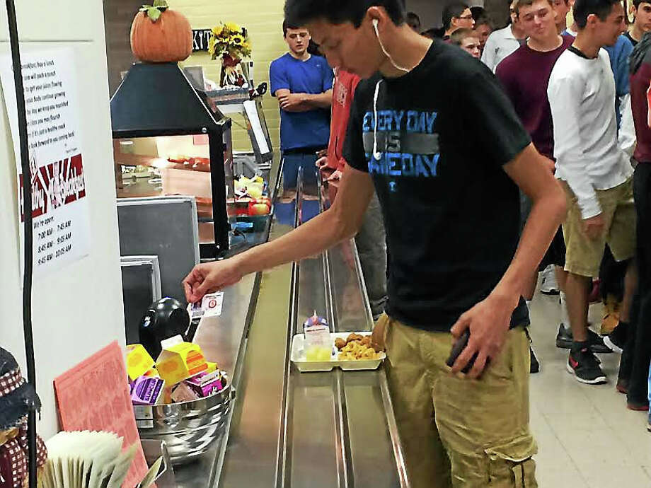 A Cheshire High School student uses a bar code on his identification card to pay for his school lunch Thursday. Photo: Luther Turmelle — New Haven Register
