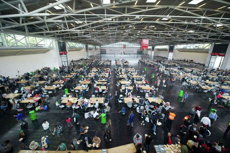 Refugees rest inside the refugee reception facility at the trade fair in Munich, Germany, Monday, Sept. 7, 2015. Photo: Angelika Warmuth/dpa Via AP    / dpa