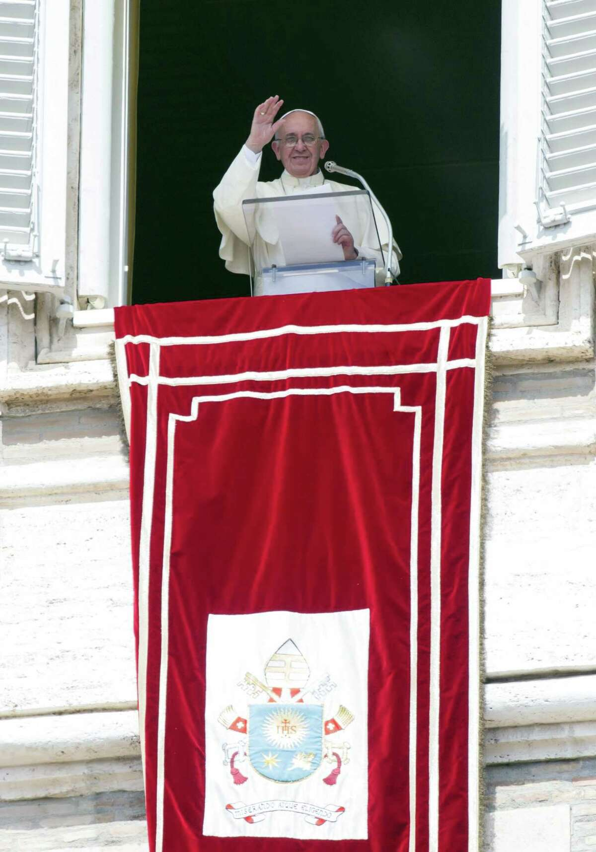 """Pope Francis delivers his blessing during the Angelus noon prayer from his studio window overlooking St. Peter's Square at the Vatican, Sunday, Sept. 6, 2015. The Vatican will shelter two families of refugees """"who are fleeing death"""" from war or hunger, Pope Francis announced Sunday as he called on Catholic parishes, convents and monasteries across Europe to do the same."""