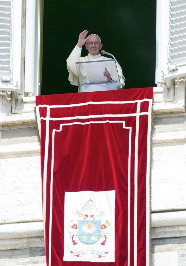"""Pope Francis delivers his blessing during the Angelus noon prayer from his studio window overlooking St. Peter's Square at the Vatican, Sunday, Sept. 6, 2015.  The Vatican will shelter two families of refugees """"who are fleeing death"""" from war or hunger, Pope Francis announced Sunday as he called on Catholic parishes, convents and monasteries across Europe to do the same. Photo: AP Photo/Riccardo De Luca   / AP"""