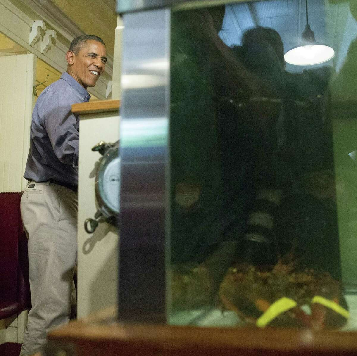 President Barack Obama greets people at Ye Olde Union Oyster House, Monday, Sept. 7, 2015, in Boston. Obama signed an Executive Order requiring federal contractors to offer their employees up to seven days of paid sick leave per year.