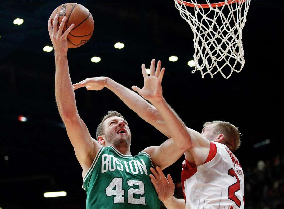 The Boston Celtics' David Lee, left, shoots over Olimpia Milano's Robbie Hummel during Tuesday's exhibition game near Milan, Italy.